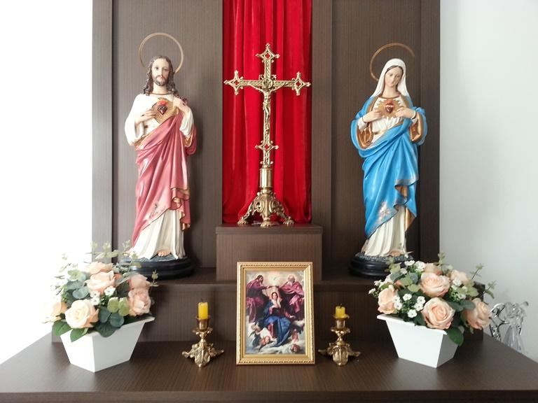Este é o oratório daqui de casa, com as imagens de Jesus e Maria, um crucifixo, e com um quadrinho que sempre mudamos de acordo com a festa litúrgica do mês ou do dia.
